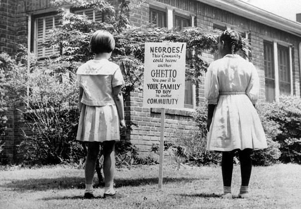 Черная и белая девочки смотрят на знак в интегрированном сообществе Лонг-Айленда в Нью-Йорке, апрель 1962 года.