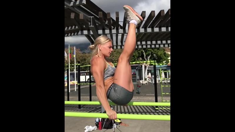 Мощная девушка тренируется на брусьях. Malin Jansson